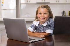 Ung härlig och söt liten flicka 6 till 8 gamla år med blont hår och blåa ögon som sitter hemmastatt kök som tycker om med bärbara Arkivbild