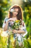 Ung härlig röd hårkvinna som rymmer en bukett för lösa blommor i en solig dag Stående av den attraktiva långa hårkvinnlign med bl Fotografering för Bildbyråer
