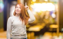Ung härlig rödhårig mankvinna över vit bakgrund royaltyfri fotografi