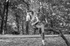 Ung härlig sexig flickamodell av det europeiska utseendet med långt hår i en skjorta och jeans som sitter på ett träd under en gå Royaltyfri Foto