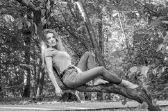 Ung härlig sexig flickamodell av det europeiska utseendet med långt hår i en skjorta och jeans som sitter på ett träd under en gå Royaltyfria Bilder