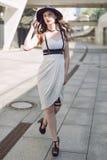Ung härlig sexig kvinna som bär den moderiktiga dräkten, den vita klänningen, den svarta hatten och läderswordbelt Longhaired bru Royaltyfria Foton