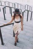 Ung härlig sexig kvinna som bär den moderiktiga dräkten, den vita klänningen, den svarta hatten och läderswordbelt Longhaired bru Royaltyfri Bild