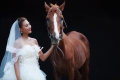 Ung härlig skönhetbrud i för bröllopdräkt för mode den vita ställningen med den stiliga hästen på svart bakgrund royaltyfria foton