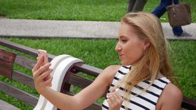 Ung härlig slank kvinna med långt blont hår i svartvit klänningdanandeselfie på mobiltelefonen över bakgrund lager videofilmer
