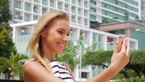 Ung härlig slank kvinna med långt blont hår i svartvit klänningdanandeselfie på mobiltelefonen över bakgrund arkivfilmer