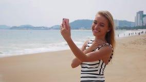 Ung härlig slank kvinna med långt blont hår i svartvit klänningdanandeselfie på mobiltelefonen nära havet på lager videofilmer