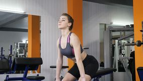 Ung härlig sportig flicka som gör böjelse-över rader med skivstången i idrottshall 60 fps lager videofilmer