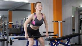 Ung härlig sportig flicka som gör böjelse-över rader med skivstången i idrottshallen, slut upp, fps för sikt för främre sida 60 stock video