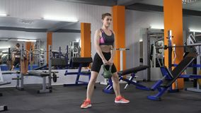 Ung härlig sportig flicka som gör vägde squats med en kettlebell i idrottshall, fps för sikt för främre sida 60 stock video