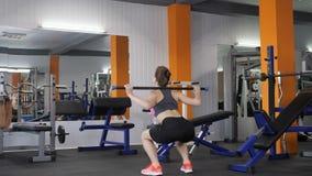 Ung härlig sportig flicka som squatting med en stång i en sportidrottshall, fps för sikt för tillbaka sida 60 lager videofilmer