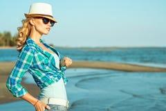 Ung härlig stilfull blond dam i spegelförsedd solglasögon och sugrör Panama på sjösidan royaltyfria bilder