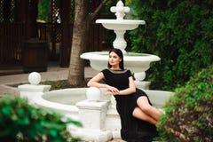 Ung härlig stilfull flicka som går och poserar i kort svart klänning i stad nära springbrunnar Utomhus- sommarstående av royaltyfria foton
