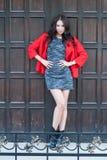 Ung härlig stilfull kvinna som är iklädd ett rött lag, grå stucken klänning, svarta kängor, mot bakgrunden av en trädörr Str Royaltyfria Bilder