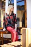 Ung härlig stilfull kvinna som poserar på den utskrivavna gatan i blom- Arkivbilder