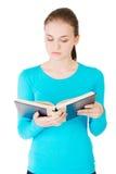 Ung härlig student som läser en bok Royaltyfria Bilder