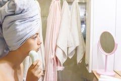 Ung härlig tonårig flicka i en handduk som gör ansikts- massage av henne fotografering för bildbyråer