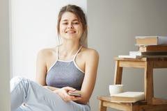 Ung härlig tonårs- flicka som surfar internet på telefonen som ler se kamerasammanträde på golv bland gamla böcker nära Royaltyfria Bilder