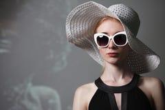Ung härlig trendig kvinna med moderiktig makeup Modellera att se kameran, bärande stilfullt glasögon, hatt Kvinnligt mode, är royaltyfri foto