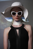 Ung härlig trendig kvinna med moderiktig makeup Modellera att se kameran, bärande stilfullt glasögon, hatt Kvinnligt mode, är royaltyfria foton