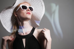 Ung härlig trendig kvinna med moderiktig makeup Modellera att se kameran, bärande stilfullt glasögon, hatt Kvinnligt mode, är fotografering för bildbyråer