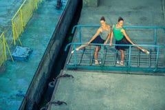 Ung härlig tvilling- dansbalett för syster två i staden med balettdräkten stads- synkroniseringsdans industriell gatadans med royaltyfria foton