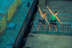 Ung härlig tvilling- dansbalett för syster två i staden med balettdräkten stads- synkroniseringsdans industriell gatadans med royaltyfri bild