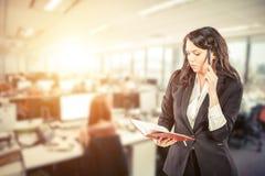 Ung hållande notepad för affärskvinna och samtal på mobiltelefonen royaltyfri bild