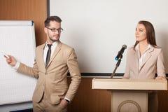 Ung hållande presentation för affärskvinna och för affärsman royaltyfri foto