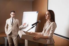 Ung hållande presentation för affärskvinna och för affärsman arkivbilder
