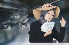 Ung hållande sedel för affärskvinna över abstrakt bakgrund med symboler Arkivfoto