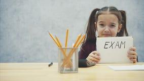 Ung hård-haired flicka som sitter på tabellen Under denna inskrift i händerna av examen Har en beklagansvärd blick stock video