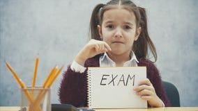 Ung h?rd-haired flicka som sitter p? tabellen Under denna inskrift i h?nderna av examen stock video
