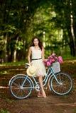 Ung h?rlig, elegantly kl?dd kvinna med den retro cykeln Sunt och att cykla fotografering för bildbyråer