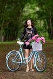 Ung h?rlig, elegantly kl?dd kvinna med den retro cykeln Sunt och att cykla arkivfoto