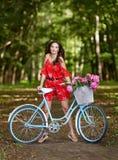 Ung h?rlig, elegantly kl?dd kvinna med den retro cykeln Sunt och att cykla royaltyfri bild