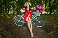 Ung h?rlig, elegantly kl?dd kvinna med den retro cykeln Sunt och att cykla royaltyfri fotografi