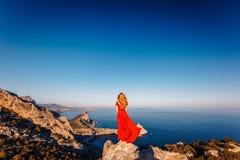 Ung h?rlig kvinna i den r?da kl?nningen som ser till berghavet royaltyfri foto
