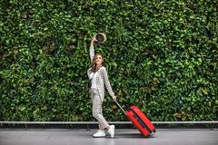 Ung h?rlig kvinna i flygplats mot den gr?na v?ggen arkivfoton