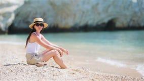Ung h?rlig kvinna p? den tropiska stranden f?r vit sand Caucasian flicka i hattbakgrund havet lager videofilmer