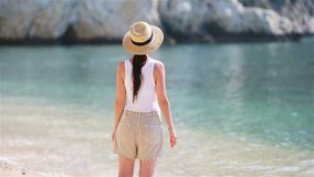 Ung h?rlig kvinna p? den tropiska stranden f?r vit sand Caucasian flicka i hattbakgrund havet stock video