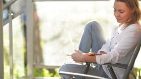 Ung h?rlig kvinna som l?ser intressera boken p? terrass, under Sunny Day stock video