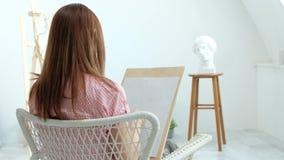 Ung h?rlig kvinnam?lare bland staffli och kanfaser i en ljus studio Inspiration och hobby arkivfilmer