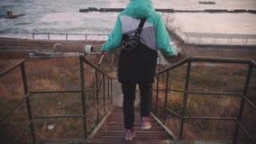 Ung h?rlig kvinnlig som g?r p? trappan som leder till stranden p? solnedg?ngen l?ngsam r?relse arkivfilmer