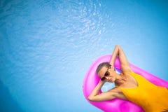 Ung h?rlig Suntanned kvinna som kopplar av bredvid en simbass?ng royaltyfri bild