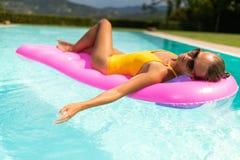 Ung h?rlig Suntanned kvinna som kopplar av bredvid en simbass?ng arkivbild