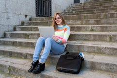 Ung h?rlig ton?ringstudentflicka som utomhus arbetar och studerar p? b?rbara datorn i en europeisk stad royaltyfria bilder