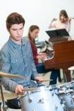 Ung handelsresande med trumpinnar i musikgrupp Royaltyfri Foto