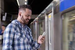 Ung handelsresande på en drevplattform som lyssnar till musik på en smartphone Begrepp av pendlingssträckan, resa, anslutning royaltyfri bild