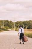 Ung handelsresande som bort går med resväskan Royaltyfria Bilder